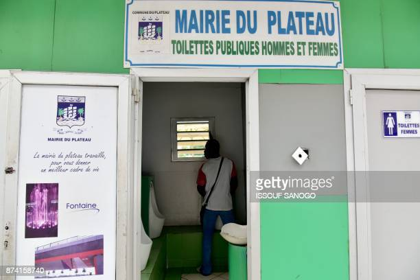 A man uses a urinal at a public toilet in the Plateau business district of Abidjan on November 14 2017 / AFP PHOTO / ISSOUF SANOGO