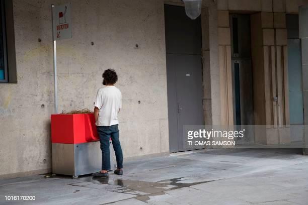 A man uses a 'uritrottoir' public urinal on August 13 near the Gare de Lyon in Paris The city of Paris has begun testing 'uritrottoirs' dry public...