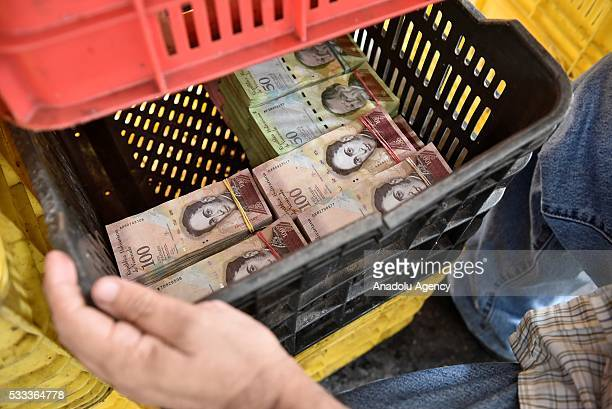 A man uses a vegetables container to put a large amount of bills of the sales of days in a local market in Caracas Venezuela on May 21 2016...