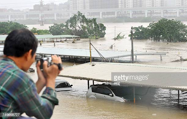 A man uses a video camera to record vehicles half submerged in floodwaters in New Taipei City on August 2 2012 Typhoon Saola pounded Taiwan with...