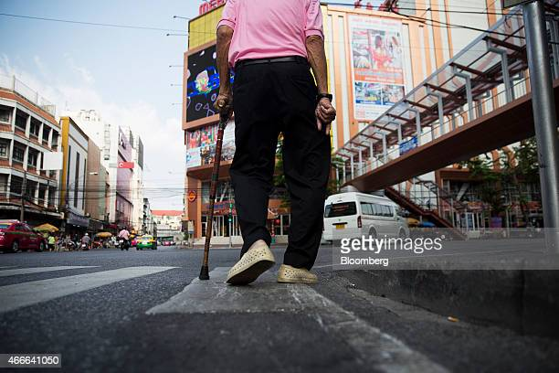 A man uses a walking cane as he walks along a road in the Chinatown area of Bangkok Thailand on Sunday March 15 2015 Almost a third of Thailand's...