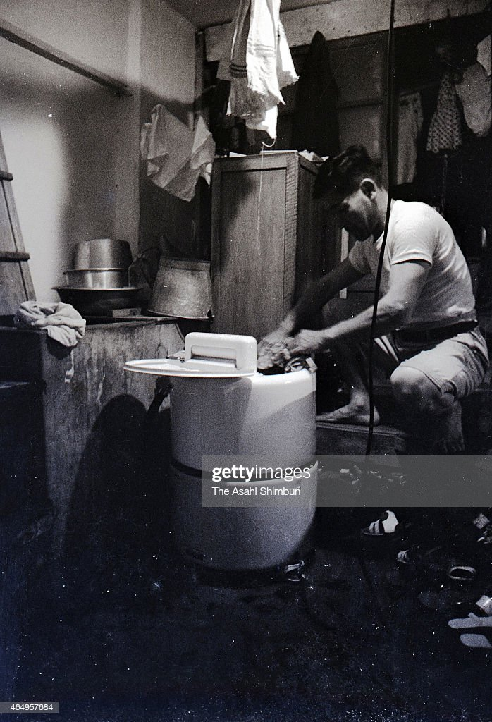 A man uses a washing machine at the concrete apartment at Hashima on August 12, 1956 in Takashima, Nagasaki, Japan. The coal mining island, is also known as the Battleship Island, whose population used to be more than 5,000 in its heyday in 1959. In the residential area there were the Japan's first concrete building apartments.
