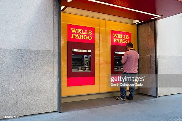 A man uses a Wells Fargo Automated Teller Machine outside headquarters of Wells Fargo Capital Finance the commercial banking division of Wells Fargo...