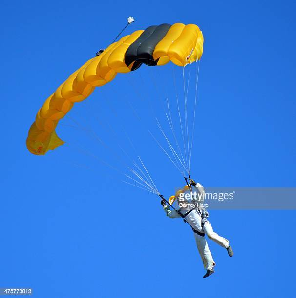 Man uses a yellow parachute after jumping from a plane. Thrill seeker, dare devil, profession skydive