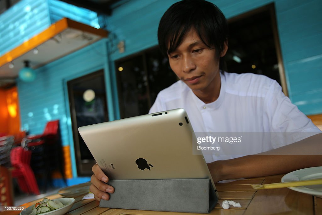 A man uses an Apple Inc. iPad at a restaurant in Yangon, Myanmar, on Tuesday, Nov. 20, 2012. Myanmar's growth outlook has improved 'substantially' amid political reforms, which are expected to lead to a large influx of foreign investment, the Organization for Economic Cooperation and Development (OECD) said on Nov. 18. Photographer: Dario Pignatelli/Bloomberg via Getty Images