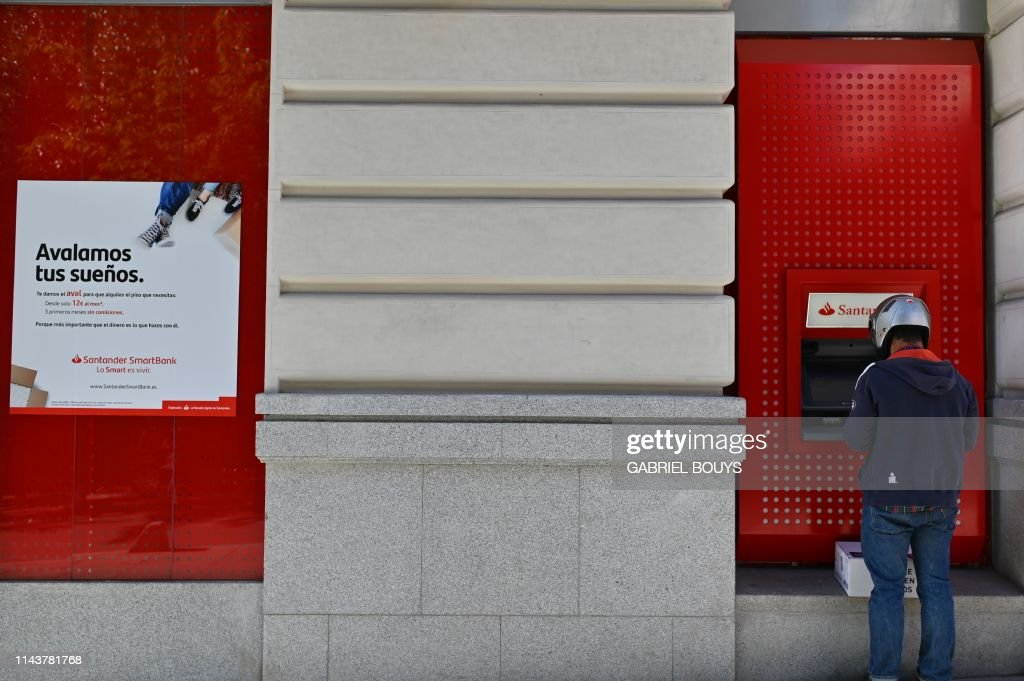 A man uses an ATM machine at a Santander bank in Madrid on