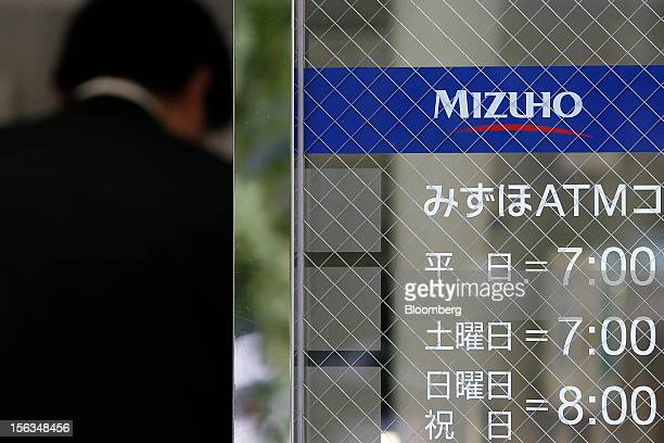 Man uses an automated teller machine at a Mizuho Bank Ltd. Branch in Tokyo, Japan, on Tuesday, Nov. 13, 2012. Mizuho Financial Group Inc. Is...