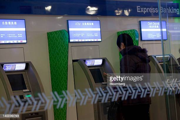 A man uses an automated teller machine at a Standard Chartered Plc bank branch in Hong Kong China on Monday Feb 27 2012 Standard Chartered is...