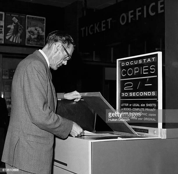 Man uses an early photocopier at London's Paddington Station, England, 1963.