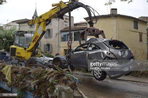 Man uses an excavator to remove a damaged car from a river following heavy rains that saw rivers bursting banks on October 15, 2018 in Villegailhenc,...