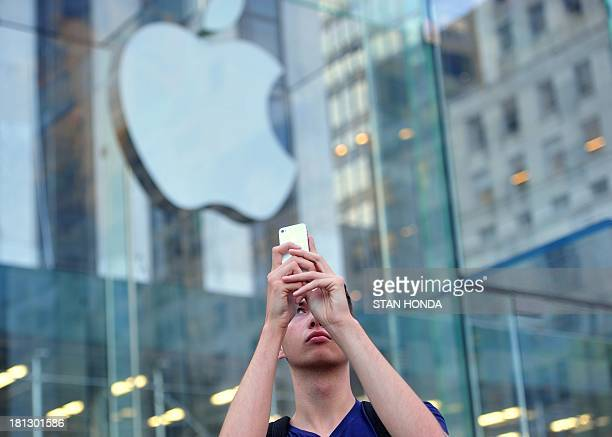 A man uses an iPhone to make a video outside the Apple Store on Fifth Avenue September 20 2013 in New York as people waited to buy the Apple iPhone 5...
