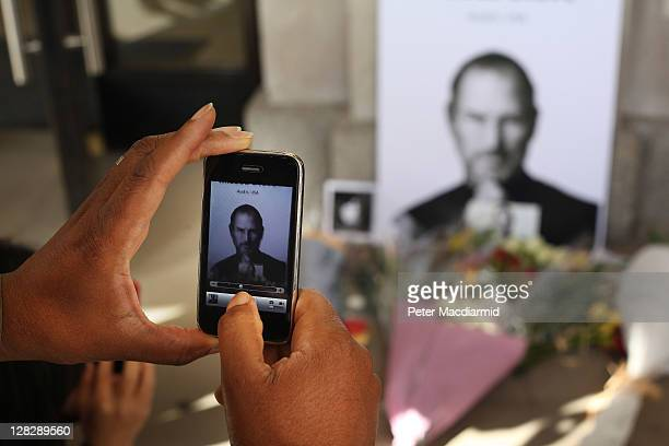 A man uses an iphone to photograph tributes to Apple Computer cofounder Steve Jobs outside The Apple Store in Covent Garden on October 6 2011 in...