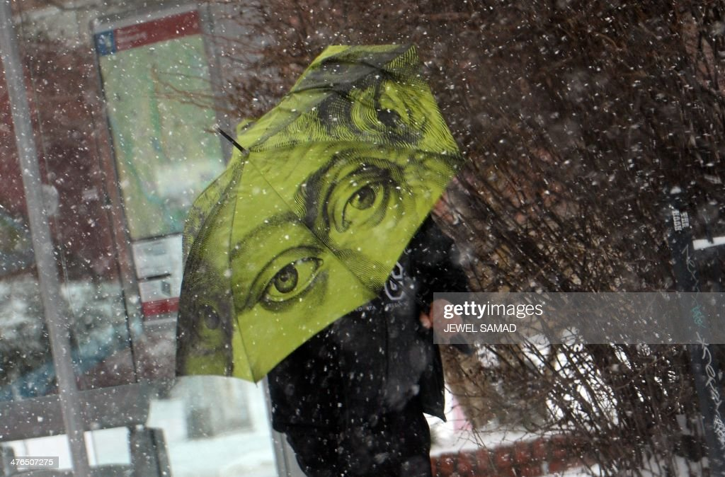 A man uses an umbrella as he makes his way during a snow storm in Washington, DC, on March 3, 2014. Another huge winter storm walloped Washington and surrounding areas on March 3, shutting schools and the federal government, snarling air traffic and blanketing roads in snow. The bitter March blast was the latest in a succession of miserable weather events that have made this one of the harshest in recent memory for residents of the US East Coast. AFP PHOTO/Jewel Samad