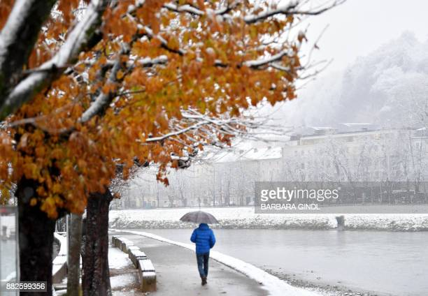 A man uses an umbrella to protect against the snow on November 30 2017 in Salzburg Austria / AFP PHOTO / APA / BARBARA GINDL / Austria OUT