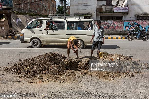 Man uses and pick axe to dig a damaged part of road in Thamal as onlookers drive past in Kathmandu on July 25, 2015 . Today marks the 3 month...