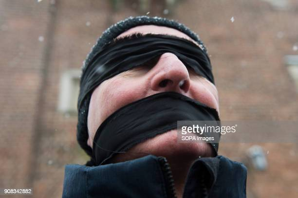 A man uses black bands over his eyes and mouth during a silent assembly named Stolen Justice in Krakow Stolen Justice happening intend to express...