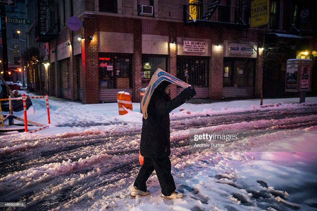 A man uses cardboard to cover himself while walking down a snowy street on February 5, 2014 in the Lower East Side neighborhood of New York, United States. New York and surrounding regions were hit with yet another snow storm today, bringing snow and ice over night, and sleet and freezing rain during theday.