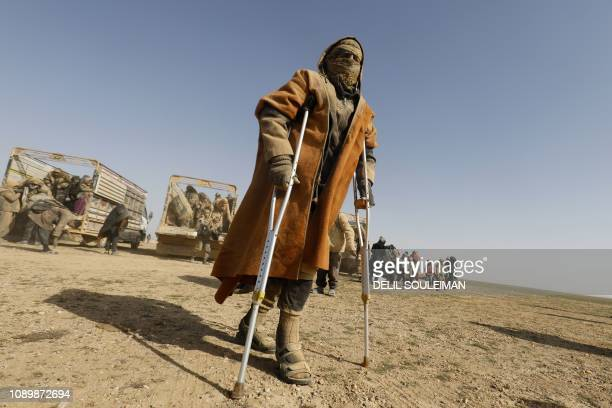 Man uses crutches to walk as people who fled battles between Syrian Democratic Forces and fighters from the Islamic State group in the Syrian village...