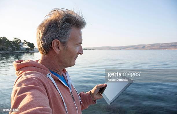 Man uses digital tablet by sea edge, selfie