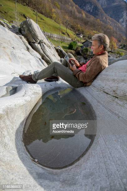 man uses digital tablet on riverbank - geografia fisica foto e immagini stock