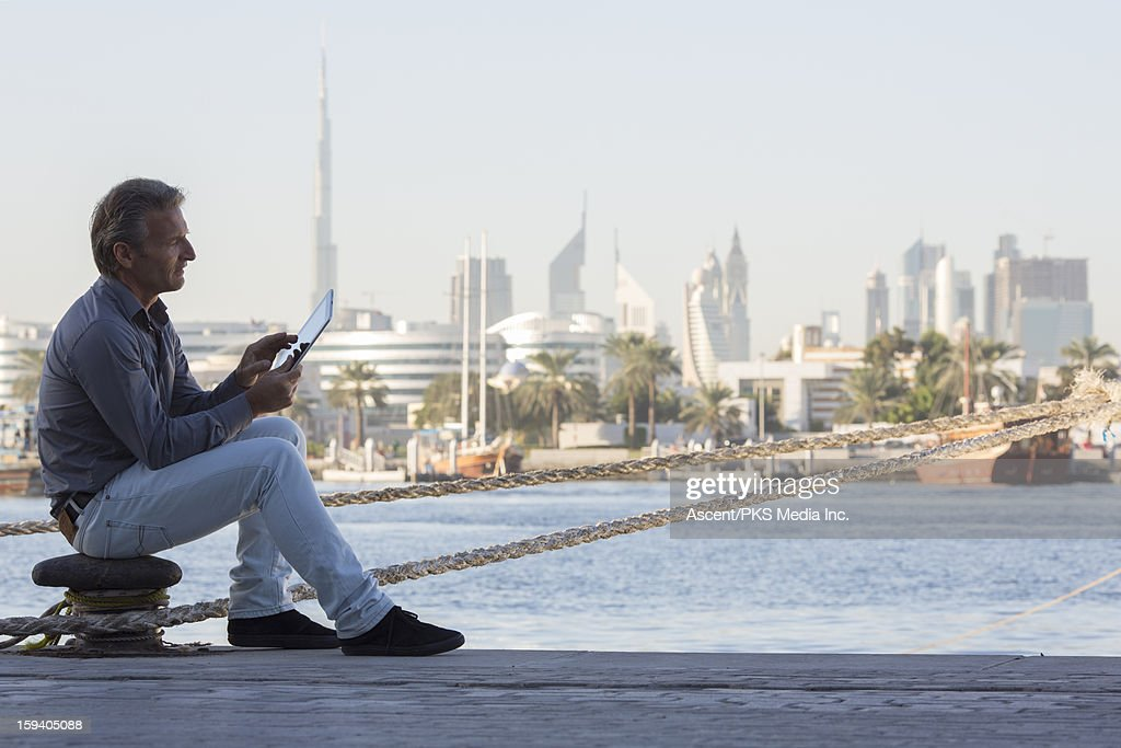 Man uses digital tablet, river and skyline behind : Stock Photo