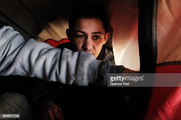 A man uses heroin in a tent under a bridge where he lives with other addicts in the Kensington section of Philadelphia which has become a hub for...
