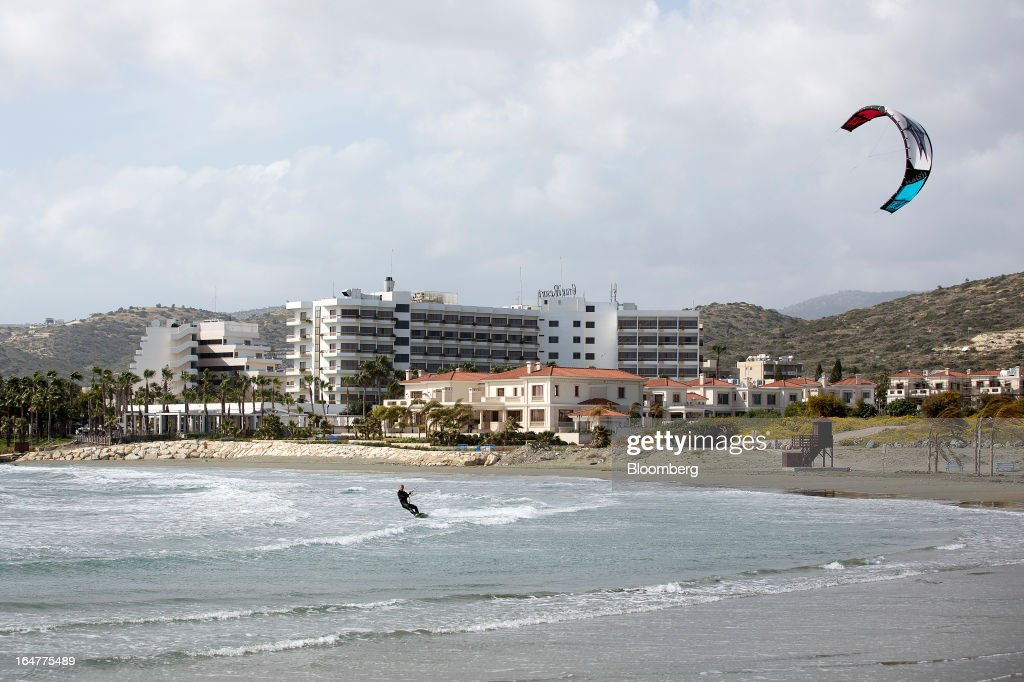 A man uses high winds to kite surf along the Mediterranean shoreline in Limassol, Cyprus, on Wednesday, March 27, 2013. The ECB said on March 25 it won't stop the Cypriot central bank from providing the island's banking sector with emergency funding. Photographer: Simon Dawson/Bloomberg via Getty Images
