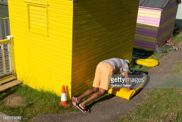 A man uses his bodyweight to deflate a large paddle board behind a bright yellow beach hut on the seafront promenade at Whitstable on 18th July 2020...