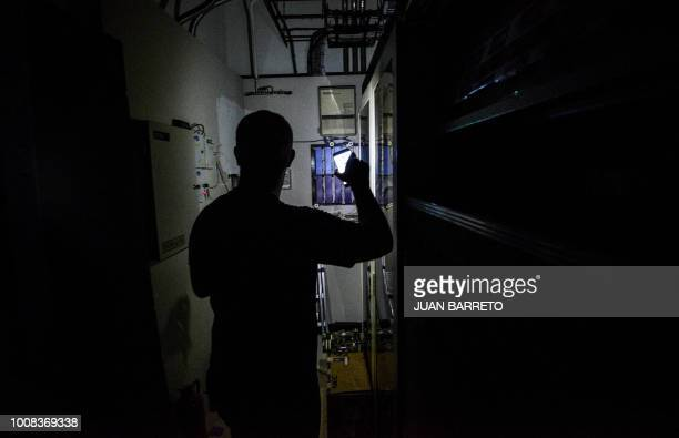 TOPSHOT A man uses his cell phone as a flashlight at his workplace during a power cut in Caracas on July 31 2018 A power failure cut electricity to...