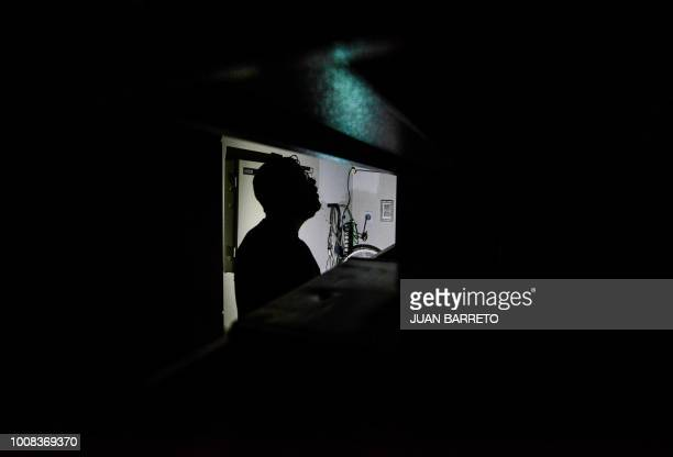 A man uses his cell phone as a flashlight at his workplace during a power cut in Caracas on July 31 2018 A power failure cut electricity to 80...