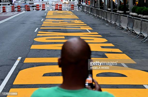 A man uses his cell phone to take a picture of a newly painted Black Lives Matter mural outside of Trump Tower on Fifth Avenue on July 10 2020 in New...