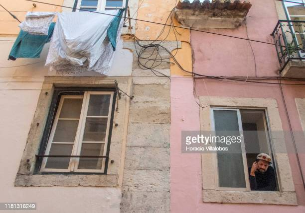 A man uses his cellphone while leaning out of a window in Calçada da Bica Pequena Santa Catarina historical neighborhood a permanent attraction for...