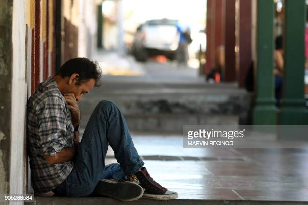 A man uses his celphone as he rests outside his home in San Isidro municipality Cabanas department 70 km northeast of San Salvador on January 13 2018...