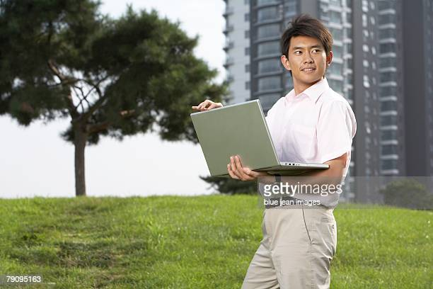 A man uses his laptop computer outside.