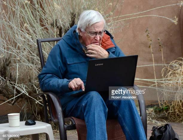 Man uses his Lenovo laptop computer on the patio of a Santa Fe, New Mexico, restaurant.