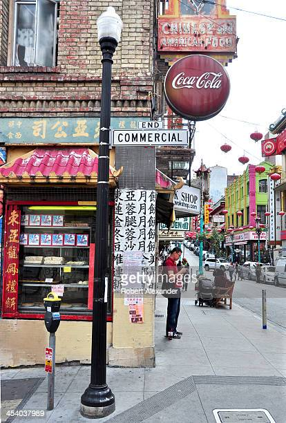 A man uses his mobile device on a street corner in San Francisco's Chinatown