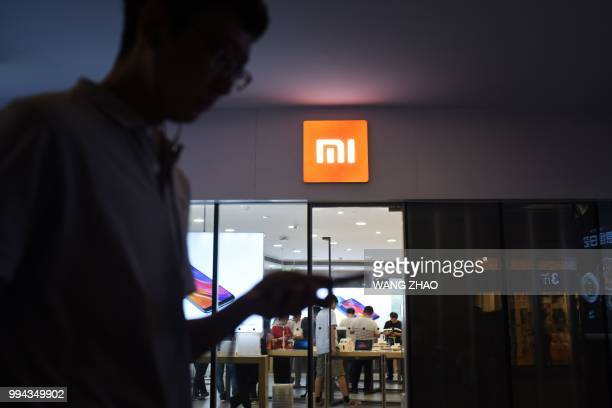 Man uses his mobile phone as he walks past a Xiaomi store in Beijing on July 9, 2018. - Shares of Chinese smartphone giant Xiaomi fell almost 6...