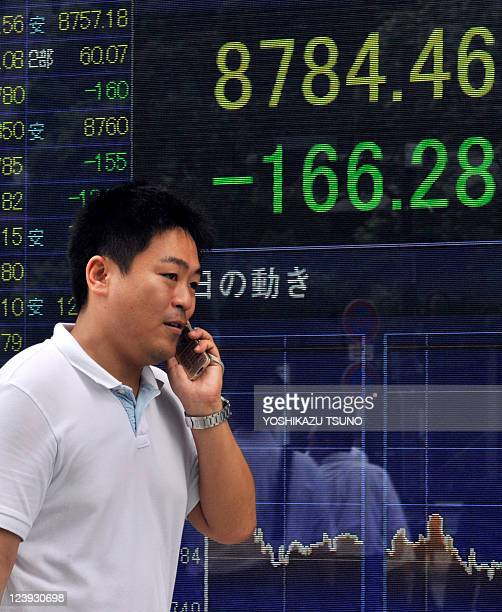 A man uses his mobile phone before a share prices board in Tokyo on September 5 2011 Japan's share prices fell 16628 points to close at 878446 points...