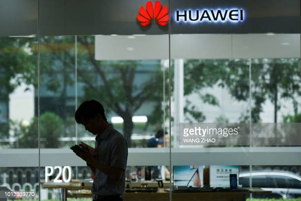 A man uses his mobile phone outside a Huawei store in Beijing on August 7 2018 Despite being essentially barred from the critical US market Huawei...