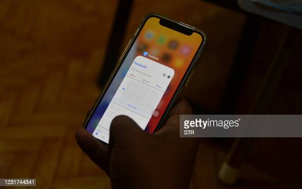 Man uses his mobile phone to check Facebook in Naypyidaw on March 16 as Myanmar authorities ordered telecommunication companies to restrict their...