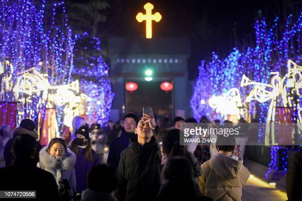 A man uses his mobile phone to take a photo at a Catholic church before a mass during the Christmas Eve in Beijing on December 24 2018