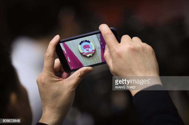 Man uses his mobile phone to take a picture during the opening session of the Chinese People's Political Consultative Conference in Beijing's Great...