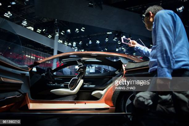 A man uses his mobile phone to take a picture of a Chery Exceed LX car at the Beijing auto show on April 26 2018 Global carmakers touted their latest...