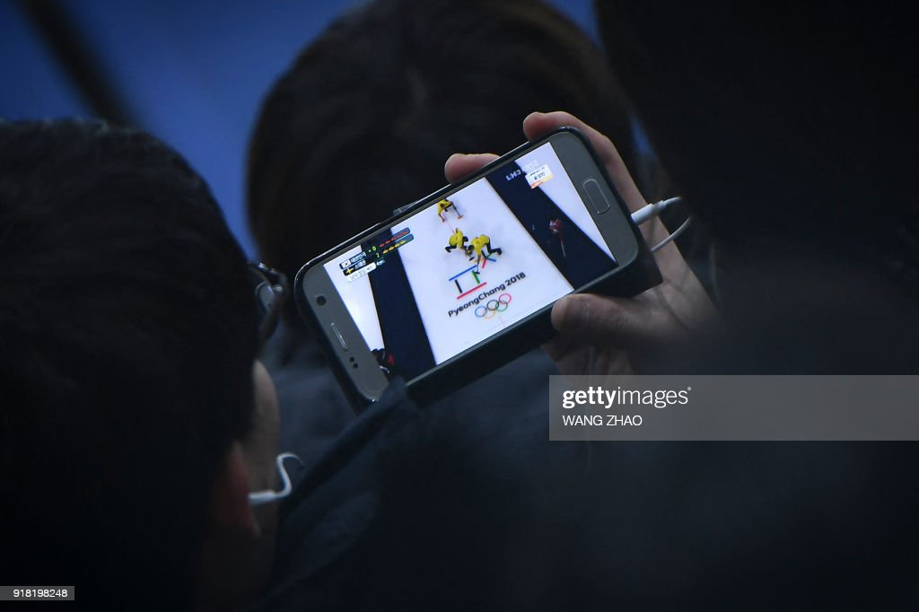 A man uses his mobile phone to watch, live, the curling men's round robin session between South Korea and Sweden during the Pyeongchang 2018 Winter Olympic Games at the Gangneung Curling Centre in Gangneung on February 14, 2018. / AFP PHOTO / WANG Zhao
