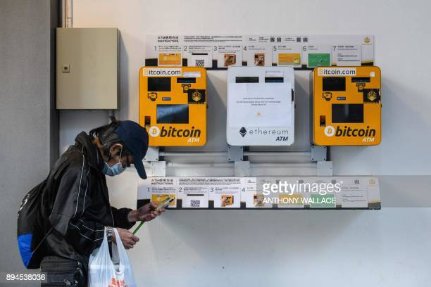 A man uses his phone as he walks past ATM machines for digital currency Bitcoin in Hong Kong on December 18 2017 Bitcoin has soared in recent weeks...