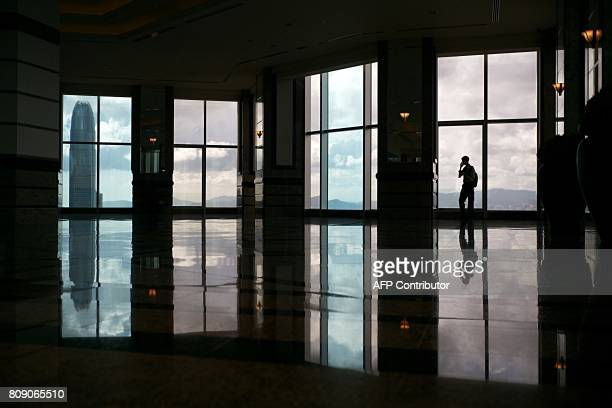 A man uses his phone on the observation floor of a highrise commercial building in Hong Kong on July 5 2017 / AFP PHOTO / Anthony WALLACE