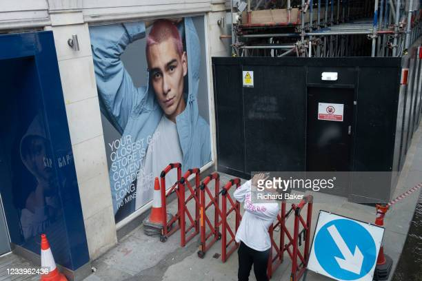 Man uses his phone to photograph the wider view of Piccadilly Circus, beneath a billboard featuring a male model, outside a brnch of GAP, on 9th July...