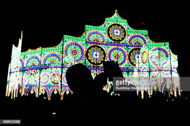 A man uses his smart phone and take picture under an illuminated structure as a part of the 21th Kobe Luminarie on December 4 2015 in Kobe Japan This...