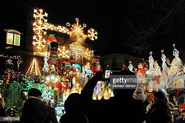 Man uses his smart phone to take a photo of a decorated house on Christmas Eve December 24, 2012 in the Dyker Heights neighborhood of the Brooklyn...