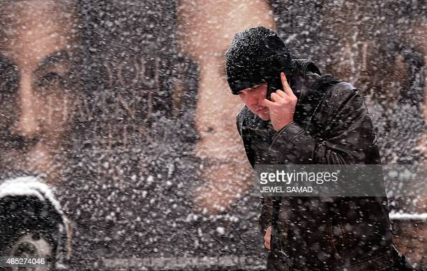 A man uses his smartphone as he crosses a street during a winter storm in New York on March 5 2015 An airplane skidded of the runway Thursday at New...